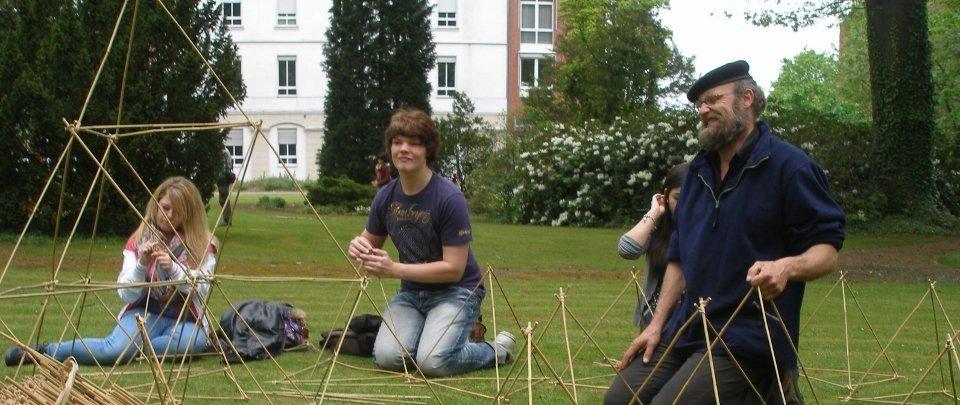 Unter der Anleitung von Robert Oude Alink werden filigrane Bambusobjekte im Park unserer Schule gebaut.