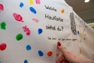 Viele bunte Fingerabdrücke ergeben auf der Stoffbahn ein buntes Bild. Foto: SMMP/Ulrich Bock